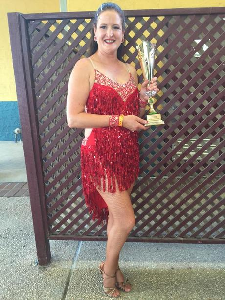Kathy Reese wearinga red dress holding her trophy